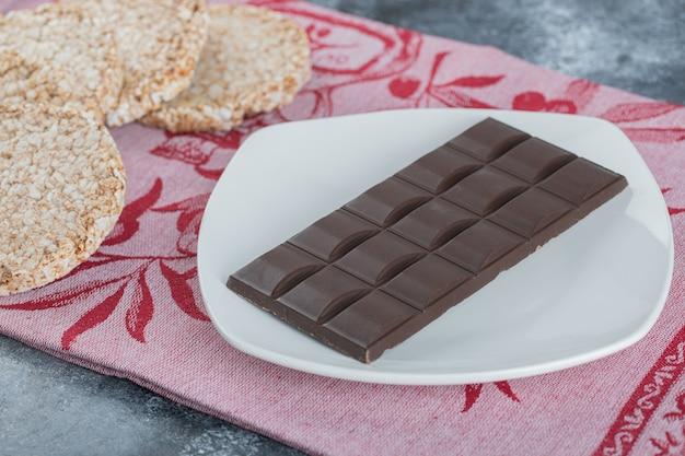 Pão de arroz crocante com barra de chocolate em uma toalha de mesa.