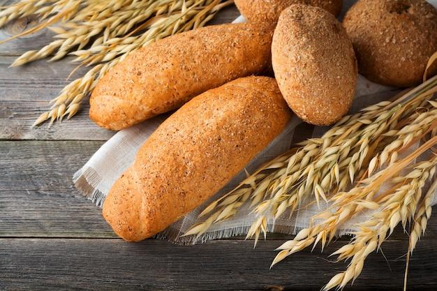 Pão de aveia integral e farinha de trigo sarraceno com espinhos na velha superfície de madeira