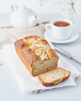 Pão de banana, bolo com banana, vista lateral, vertical. a manhã café da manhã com chá