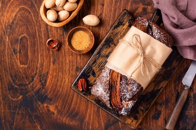 Pão de banana com crunch de canela e polvilhado com açúcar de confeiteiro sobre fundo claro de concreto. foco seletivo, espaço para texto