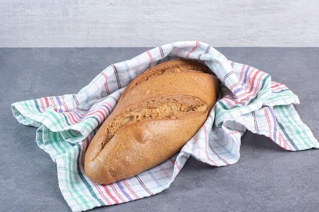 Pão de bastão envolvendo uma toalha sobre mármore.