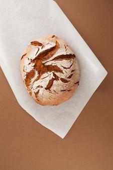 Pão de centeio acabado de cozer em fundo marrom. pão saudável sem fermento.