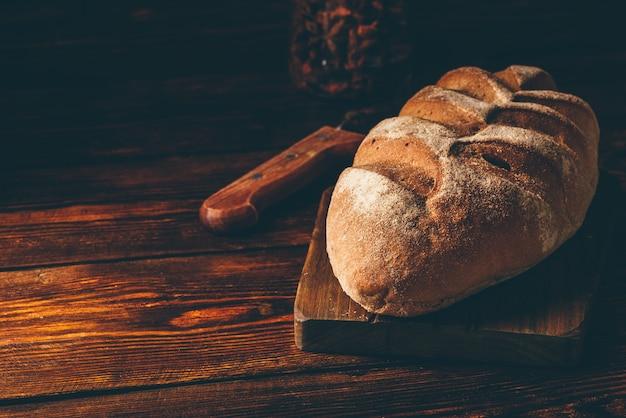Pão de centeio caseiro na tábua com faca sobre a mesa de madeira escura.