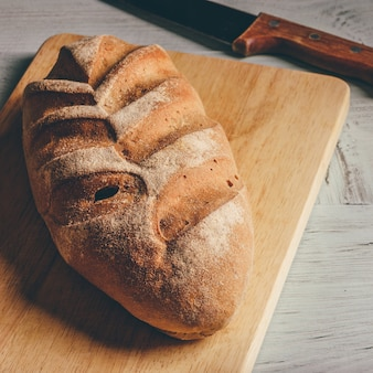 Pão de centeio caseiro na tábua com faca sobre madeira clara.