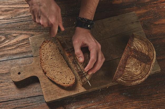 Pão de centeio colocado na placa de madeira da cozinha, chef segurando uma faca de ouro para cortar.