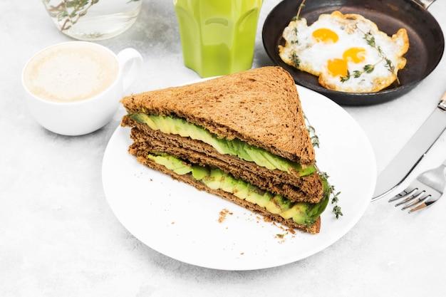 Pão de centeio com abacate, ovos fritos, limonada e café
