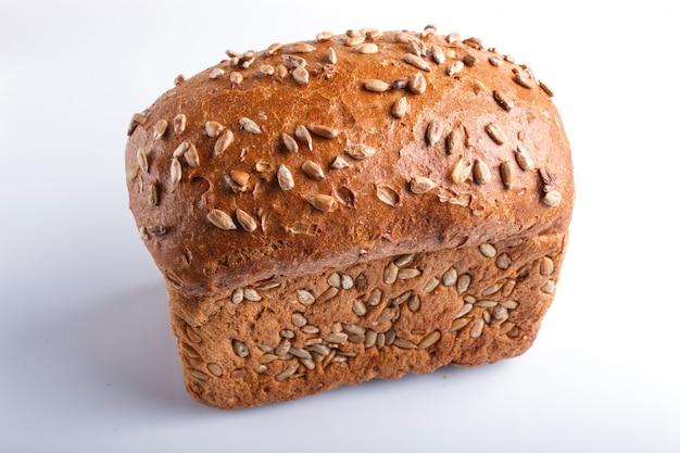 Pão de centeio com as sementes de girassol isoladas no branco.