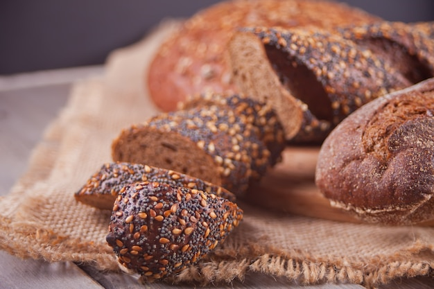 Pão de centeio com cereais e sementes na mesa da cozinha de madeira
