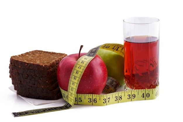 Pão de centeio com maçãs verdes e vermelhas e suco em um copo em um prato branco com uma fita métrica amarela