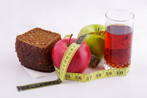 Pão de centeio com maçãs verdes e vermelhas e suco em um copo em um prato branco com uma ta ...