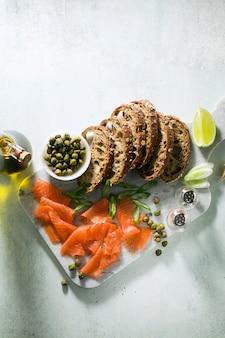 Pão de centeio com salmão defumado na placa de mármore. lanche de inverno.