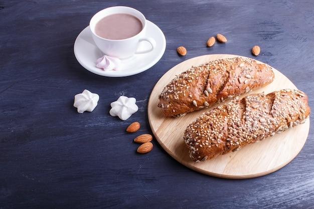 Pão de centeio com sementes de girassol, gergelim e linho com copo de cacau na superfície azul escuro.