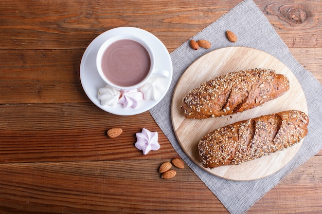 Pão de centeio com sementes de girassol, gergelim e linho com copo de cacau na superfície de madeira marrom.
