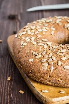 Pão de centeio com sementes de girassol na placa de madeira