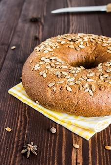 Pão de centeio com sementes de girassol na toalha na placa de madeira