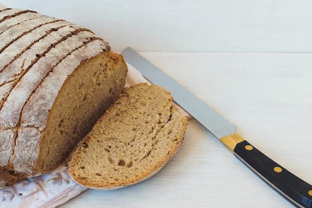 Pão de centeio cortado com uma faca. crosta e miolo escuros