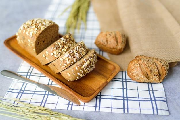 Pão de centeio de trigo integral caseiro pão é cortado e colocado sobre uma placa de madeira. e colocar em uma toalha de mesa.