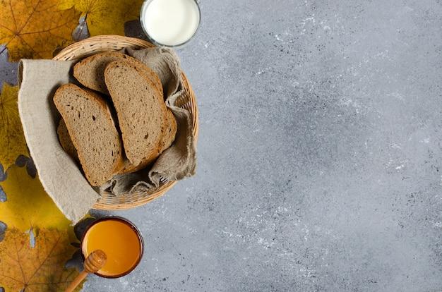 Pão de centeio é cortado em pedaços. mel, leite em um copo de vidro, folhas de plátano amarelas.