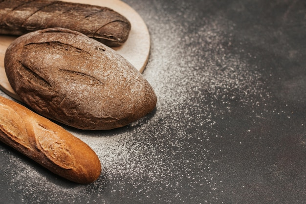 Pão de centeio e pão de trigo em um fundo cinza escuro, polvilhado com farinha