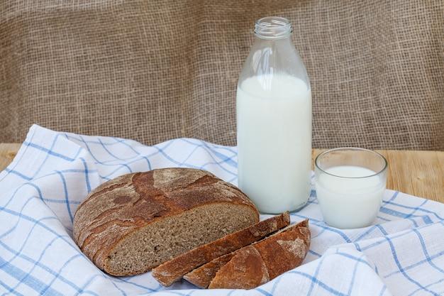 Pão de centeio fatiado com garrafa de leite na mesa de madeira