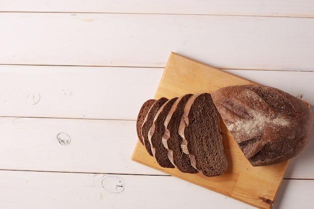 Pão de centeio fatiado em uma tábua de cortar na mesa de madeira branca