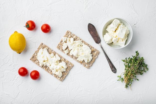 Pão de centeio fresco com conjunto de cobertura diferente, em mesa de pedra branca, vista de cima plano