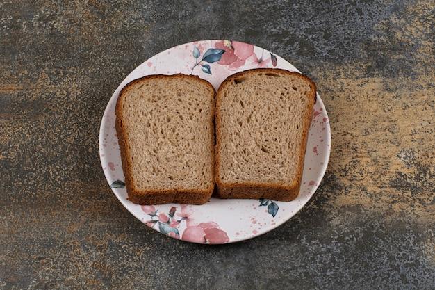 Pão de centeio fresco fatiado em prato colorido