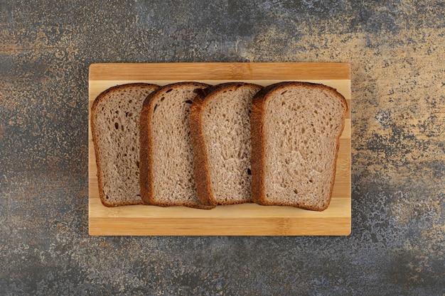 Pão de centeio fresco fatiado em tábua de madeira
