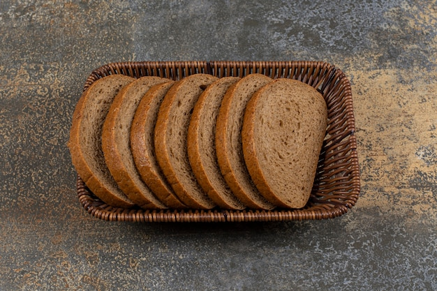 Pão de centeio fresco fatiado em uma cesta de madeira.