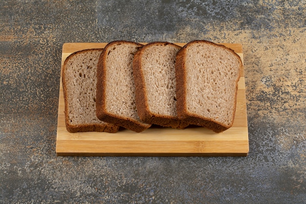 Pão de centeio fresco fatiado na placa de madeira.