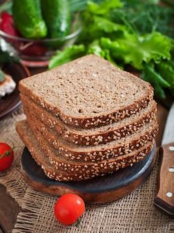 Pão de centeio integral com farelo e sementes na mesa de madeira
