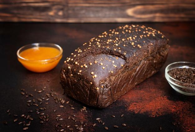 Pão de centeio integral, mel e malte em um fundo escuro de madeira. pão caseiro. foco seletivo, close-up