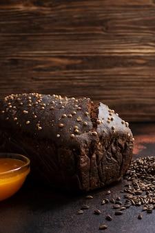 Pão de centeio integral, mel e malte em um fundo escuro de madeira. pão caseiro. vertical. foco seletivo, close-up