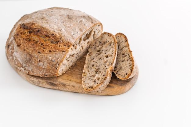 Pão de centeio integral orgânicos frescos assados na tábua de madeira
