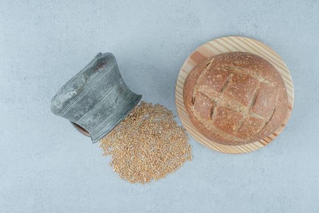 Pão de centeio na tábua de madeira com caneca de cevada