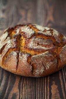 Pão de centeio quente em close-up em uma madeira