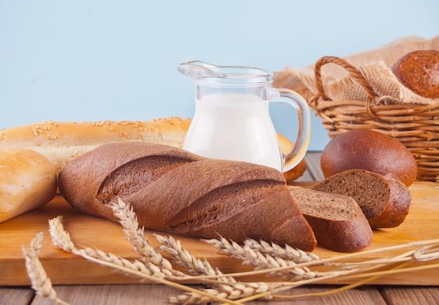 Pão de centeio recentemente cozido com cereais e sementes, jarro com leite e trigo decorre na mesa da cozinha de madeira. vista do topo.