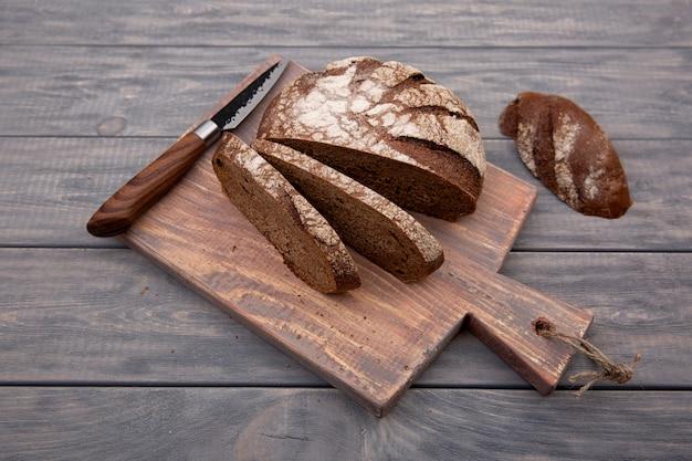 Pão de centeio redondo cortado em pedaços sobre uma tábua de madeira com uma faca de madeira rústica. vista do topo.