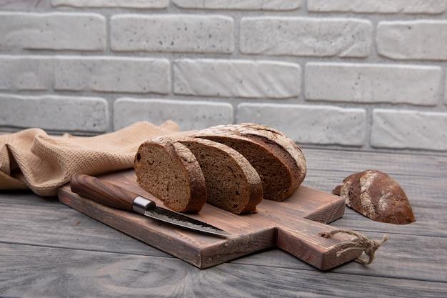 Pão de centeio redondo cortado em pedaços sobre uma tábua de madeira com uma faca de madeira rústica.