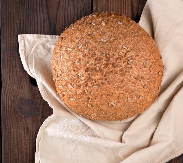 Pão de centeio redondo cozido com sementes de girassol em um guardanapo bege de têxteis