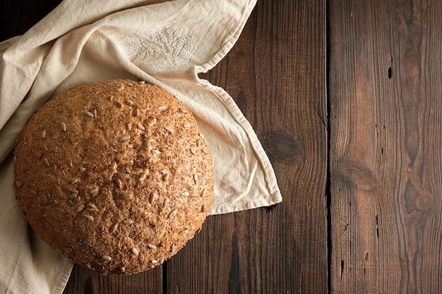 Pão de centeio redondo cozido com sementes de girassol em um guardanapo de têxteis bege