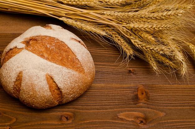 Pão de centeio redondo e espigas de trigo em uma mesa de madeira, vista superior