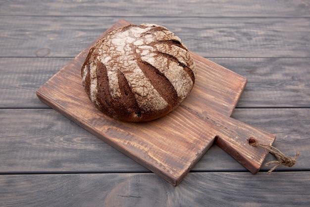 Pão de centeio redondo sobre uma placa de madeira com uma faca de madeira rústica. vista do topo.