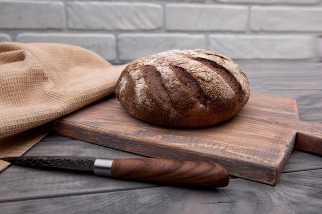 Pão de centeio redondo sobre uma placa de madeira com uma faca de madeira rústica.