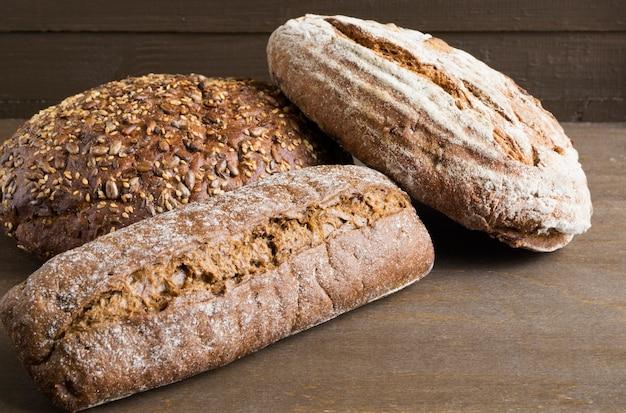 Pão de centeio rústico caseiro em um fundo escuro.