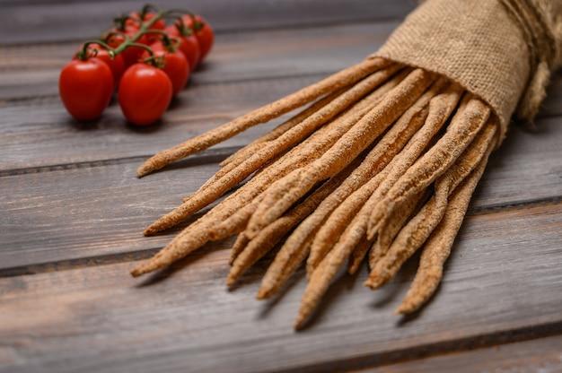 Pão de centeio tradicional italiano grissini com tomates em saco de linho com fundo de madeira.