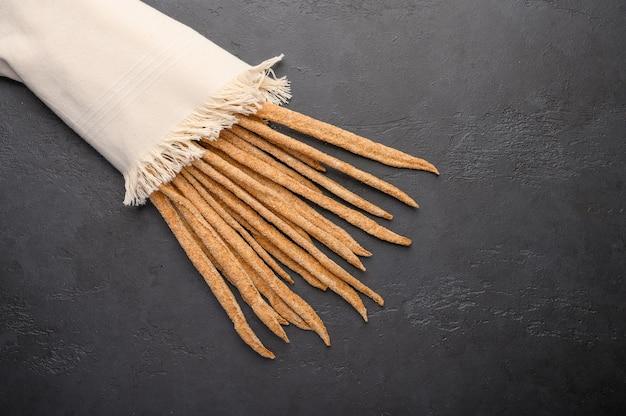 Pão de centeio tradicional italiano grissini em guardanapo de linho em fundo escuro.