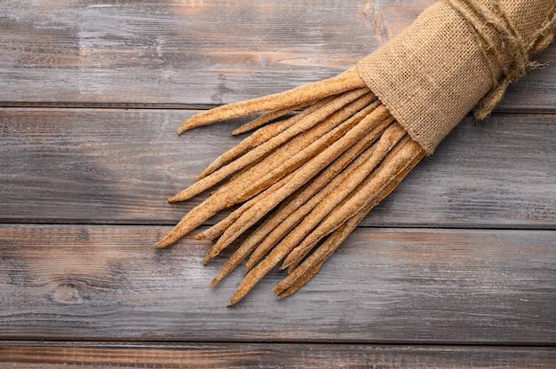 Pão de centeio tradicional italiano grissini em saco de linho com fundo de madeira.