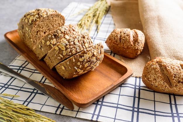 Pão de centeio trigo integral pão é cortado e colocado sobre uma placa de madeira. e colocar em uma toalha de mesa.