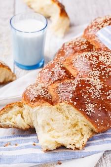 Pão de chalá com sementes de gergelim e um copo de leite, pastelaria